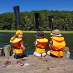 Kinder mit Paddeln auf dem Bootsteeg