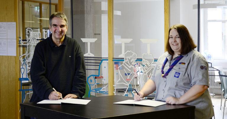 Michael Zerr und Natascha Sonnenberg stehen an einem Tisch und unterzeichnen die Vereinbarung.