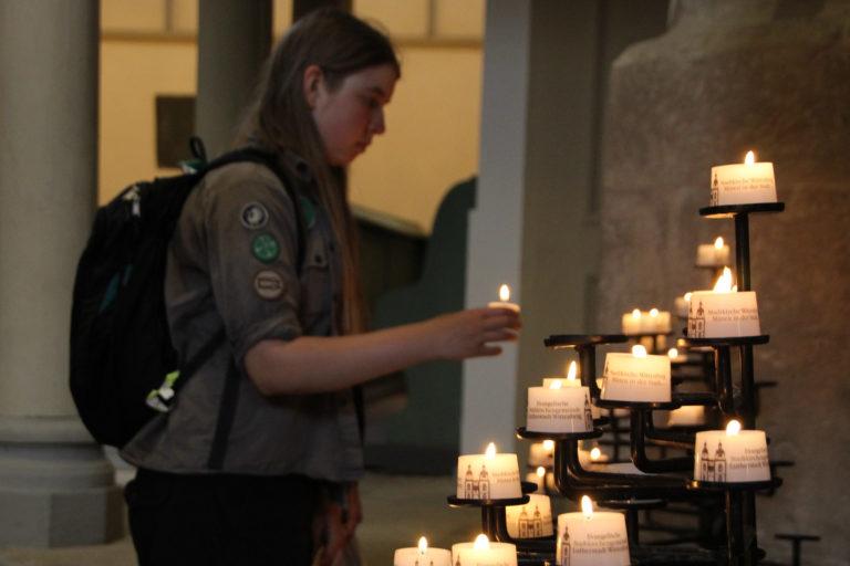Pfadfinderin zündet eine Kerze in einer Kirche an. Mehrere Kerzen brennen schon.